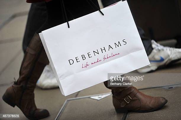 Christmas shopper on Oxford Street carrying Debenhams shopping bags on December 17 2013 in London England As Christmas Day approaches London's...