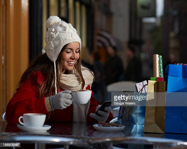 Christmas shopper using phone at coffee shop.