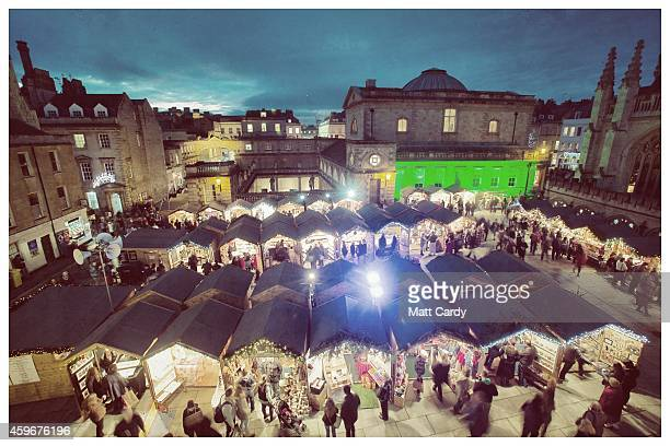 Christmas shoppers browse the stalls at the opening of the traditional Christmas market close to the historic Roman Baths and Bath Abbey on November...