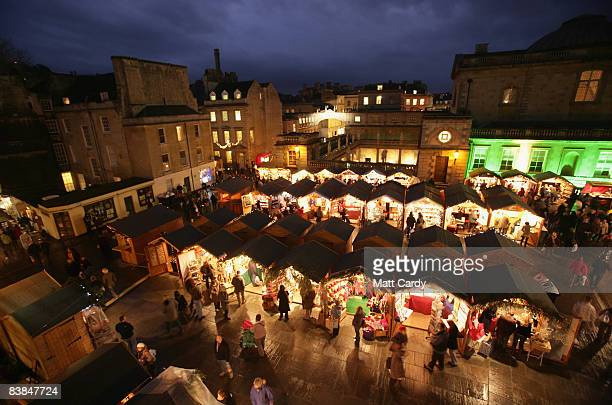 Christmas shoppers browse the stalls at the opening of the traditional Christmas market besides the historic Roman Baths and Bath Abbey on November...