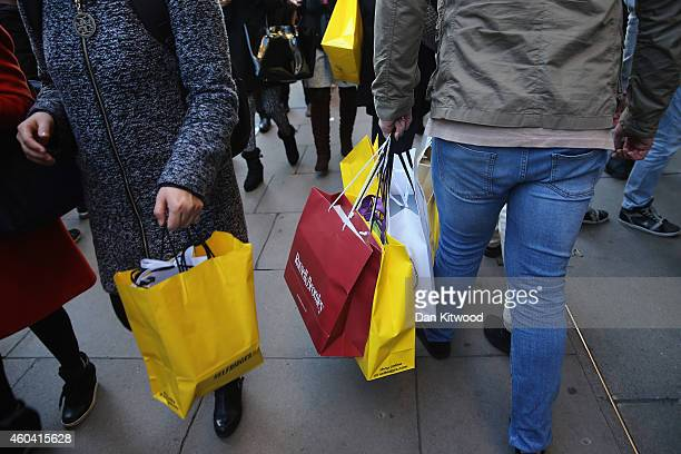 Christmas shoppers carry shopping bags as they crowd Oxford Street on December 13 2014 in London England Retailers across the UK are hoping for...