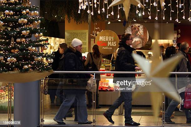 Christmas shoppers pass through a shopping mall on December 8 2012 in Berlin Germany German consumer confidence dropped prior to the Christmas season...
