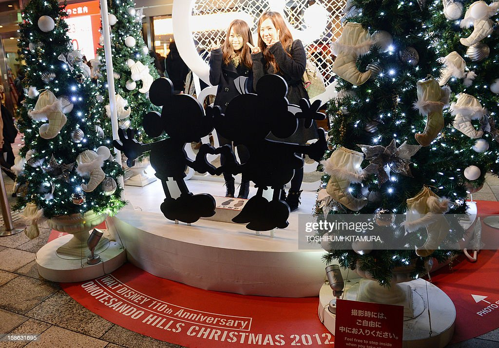 Christmas shoppers pose for a picture next to a Mickey and Minnie Mouse light display outside a shopping mall as a part of decorations ahead of Christmas in Tokyo on December 22, 2012. Although Christians only account for around only one percent of Japan's population,, people usually celebrate Christmas by spending time with their sweethearts and exchanging gifts.