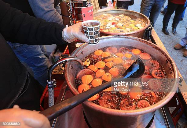 Christmas shoppers stop for mulled wine as they browse stalls at the traditional Christmas market close to the historic Roman Baths and Bath Abbey on...
