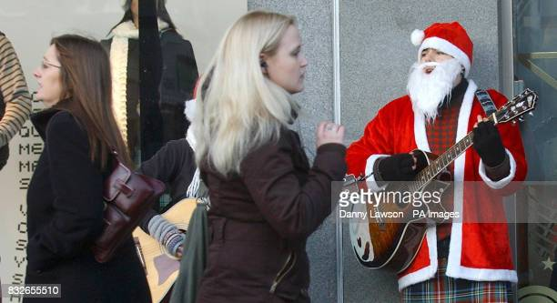 Christmas shoppers walk past busker Mark Shotter performing on Princes Street in Edinburgh after a survey by theology think tank Theos found that the...
