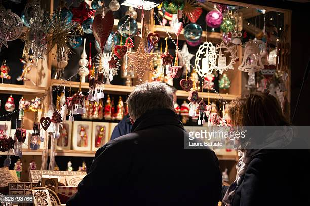Christmas Shopping - A couple is choosing ornaments in a Christmas market stall