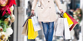 young woman walking with shopping bags in hands, christmas background