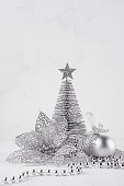 Christmas silver tree and decorations on white soft wood background. Festive interior.
