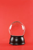 Blank snow globe with wooden base against a red background with free space for text.