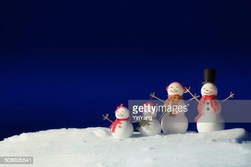 Familia pie de Navidad muñeco de nieve en la nieve en invierno noche transparente : Foto de stock
