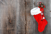 Christmas sock and wreath hanging on old barn board wood