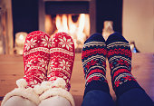 Two pairs of Christmas socks against to fireplace.