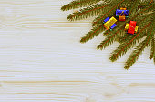 Christmas background with spruce branches and three bunches of multi colored napolitains