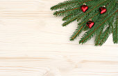 Christmas background with spruce branches and red heart pendants