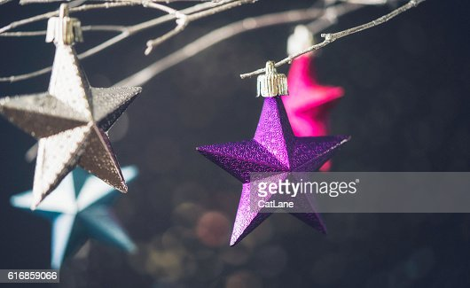 Christmas star ornaments hanging on silver branches with bokeh : Stock Photo