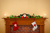 Christmas stockings hanging over the fireplace at midnight on Christmas Eve, the mantlepiece is decorated with festive holly and ivy garland plus candles. Plenty of copy space to add your own message.