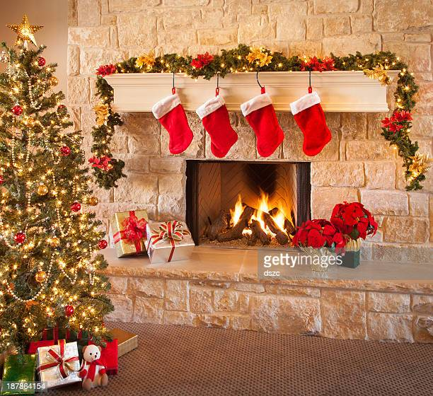 Christmas stockings, fire in fireplace, tree, and decorations
