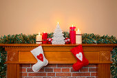Christmas stockings hanging over a fireplace with candles on the mantlepiece