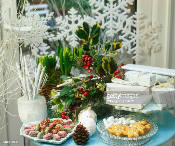 A Christmas table laid with flowers, presents, candles and biscuits in front of a window decorated with snowflakes