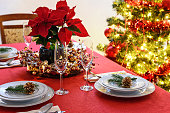 Christmas table decoration concept - champagne glasses, red poinsettia and table setting on a background of colorful Christmas decoration.