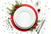 Christmas table setting with vintage dishware, silverware and red decorations on white background. Top view.