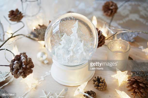 Christmas table with snow globe and fir cones