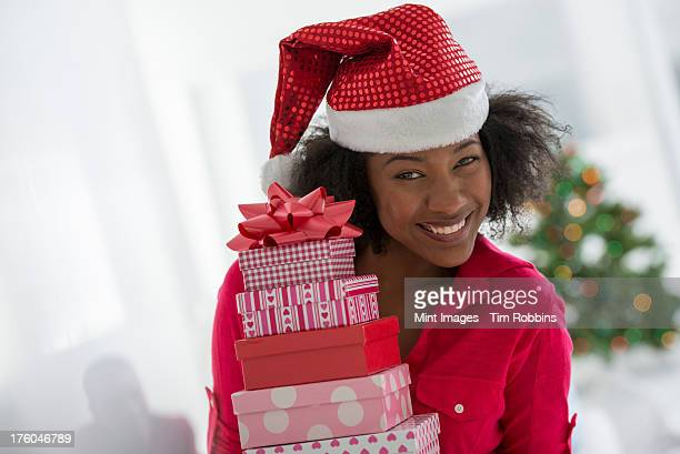 Christmas time. Celebrating the holidays. A woman wearing a red and white Father Christmas hat with a stack of Christmas presents.