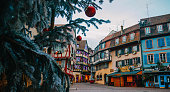 Old town decorate magical like a fairy tale in Noel festive season with detail of Christmas tree with red ball ornates at early morning time in Colmar, Alsace, France.