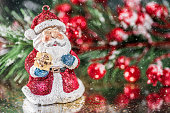 A small Santa Claus set against some holly and red berries for a bright happy Christmas scene