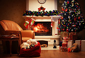 Christmas Tree and Christmas gift boxes in the interior with a fireplace. Christmas living room with fireplace and armchair