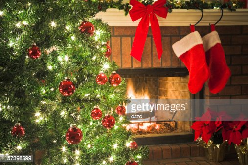 Christmas Tree And Decor Around The Fireplace With Blazing Fire