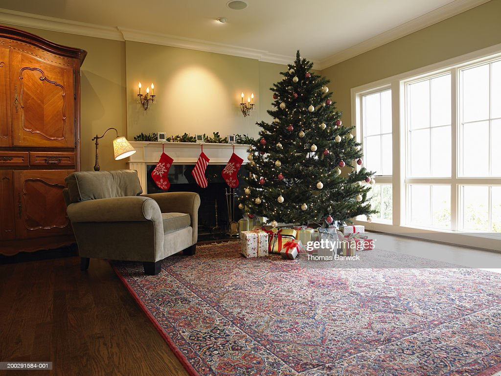 christmas tree and gifts beside fireplace in living room stock