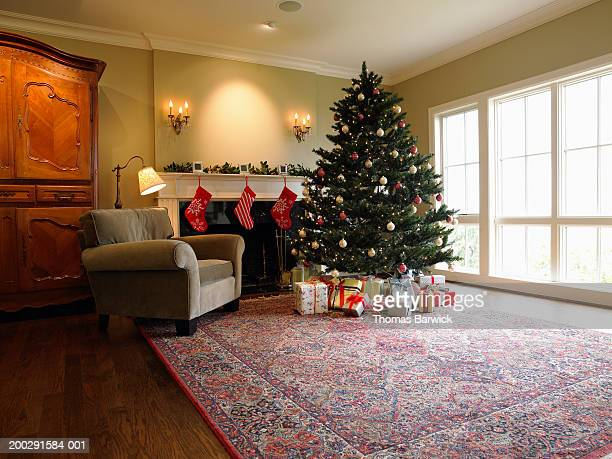 Christmas tree and gifts beside fireplace in living room