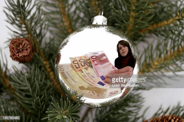 Christmas tree decoration with refection of a woman with Euro notes Symbol picture about Christmas bonus and Christmas present Montage