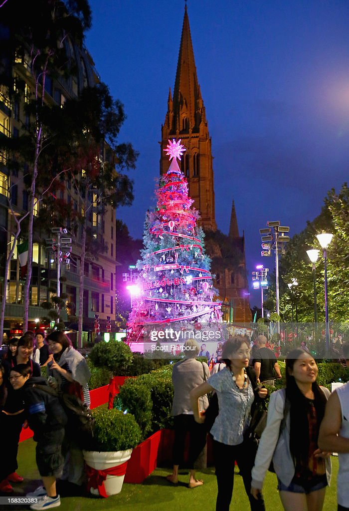 A Christmas tree is illuminated at dusk in Christmas Square as Melbourne lights up for Christmas on December 13, 2012 in Melbourne, Australia. Christmas Square stars a decorated 9.2 metre living tree and a magical forest maze where children can find Rudolph and his reindeer friends.