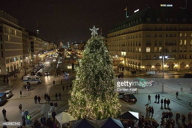A christmas tree is iluminated on the Pariser Platz in front of the Brandenburger Tor on December 16 2014 in Berlin Germany