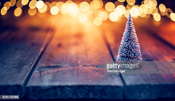 Christmas tree on old wood and defocused blue gold lights