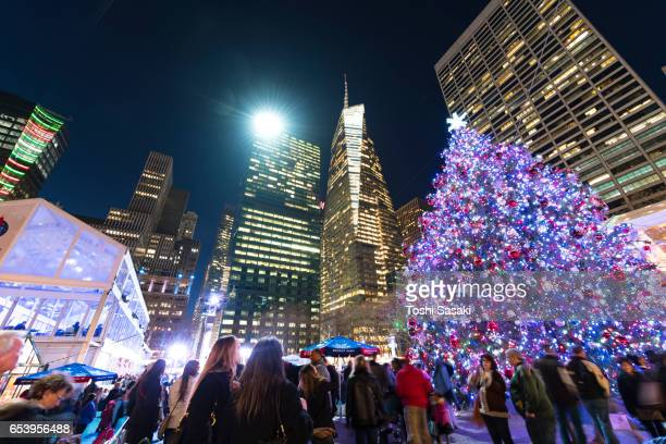 Christmas tree stands among the Midtown Manhattan Skyscrapers in the night at Bryant Park New York on Dec. 27 2016. Many tourists and visitors are around the Christmas tree.