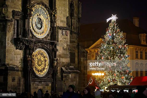A christmas tree stands behind an astronomical clock at the Christmas market at the Old Town Square on November 30 2014 in Prague Czech Republic...