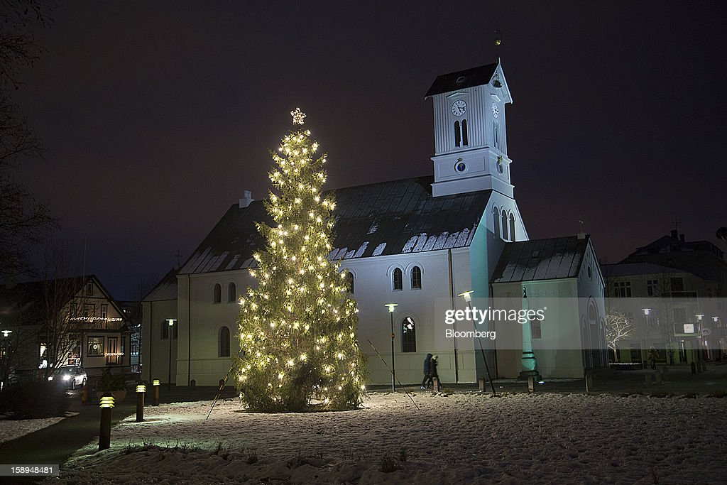 A Christmas tree stands illuminated at night outside a church in Reykjavik, Iceland, on Tuesday, Jan. 1, 2013. Creditors of Iceland's three biggest failed banks are fighting for a waiver to krona controls imposed in 2008 amid risks pay-outs will be delayed beyond 2015. Photographer: Arnaldur Halldorsson/Bloomberg via Getty Images