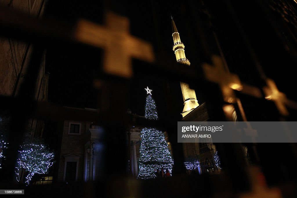 A Christmas tree stands outside Saint George church next to the Mohammed al-Amin mosque in downtown Beirut on December 23, 2012. AFP PHOTO/ANWAR AMRO