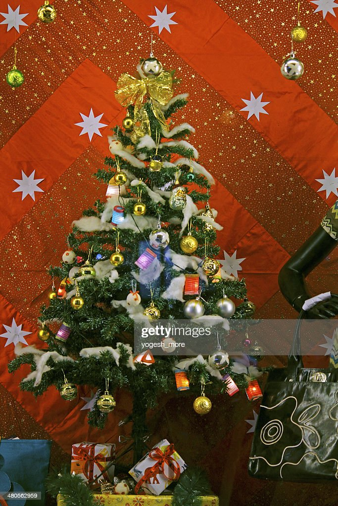 Christmas tree with bells and snowflakes and gift boxes : Stock Photo