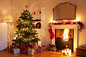 Christmas tree with gifts near fireplace