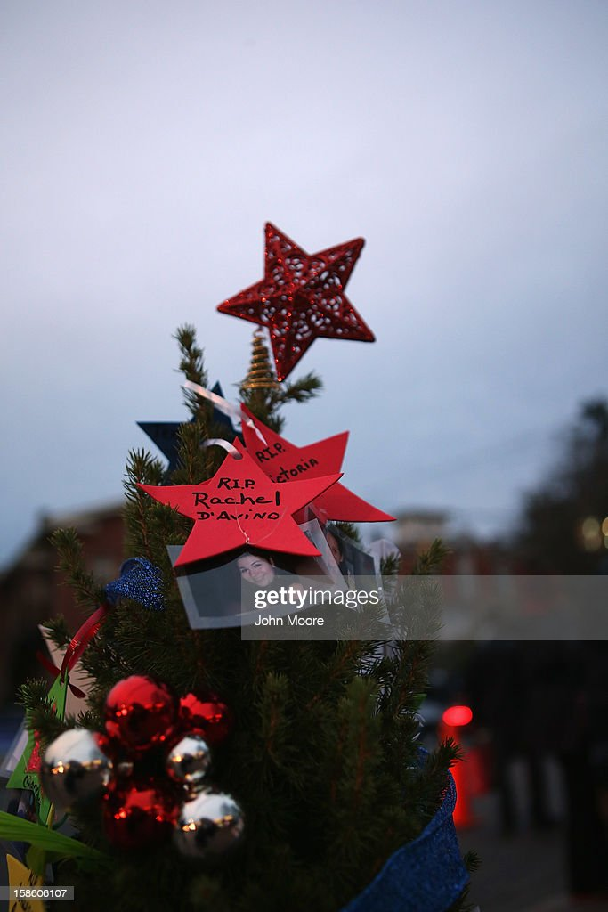 A Christmas tree with photos of people killed in last Friday's massacre stands at a streetside memorial on December 20, 2012 in Newtown, Connecticut. Six funeral services were held Thursday in the Newtown area for students and teachers slain in the attack.