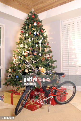 christmas tree with presents sitting and a red bicycle in corner of living room stock photo getty images - Corner Christmas Tree
