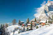 Travel to Switzerland in the winter. Alpine Village in the snow. Traditional houses with red shutters and roofs.