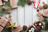 Christmas toys, decorations, presents and gift boxes wrapped in kraft paper on white wooden background, copy space