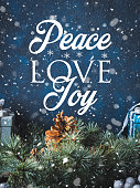 Christmas winter dark background with decorations on blue with green fir tree branches. Wishing Peace, love, Joy