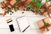Christmas online shopping. Smartphone, credit card and presents list with copy space on white wooden table with gift boxes border. Top view, preparing for winter holidays concept