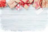 Christmas wooden background with gift boxes and snow. Top view with copy space for your text